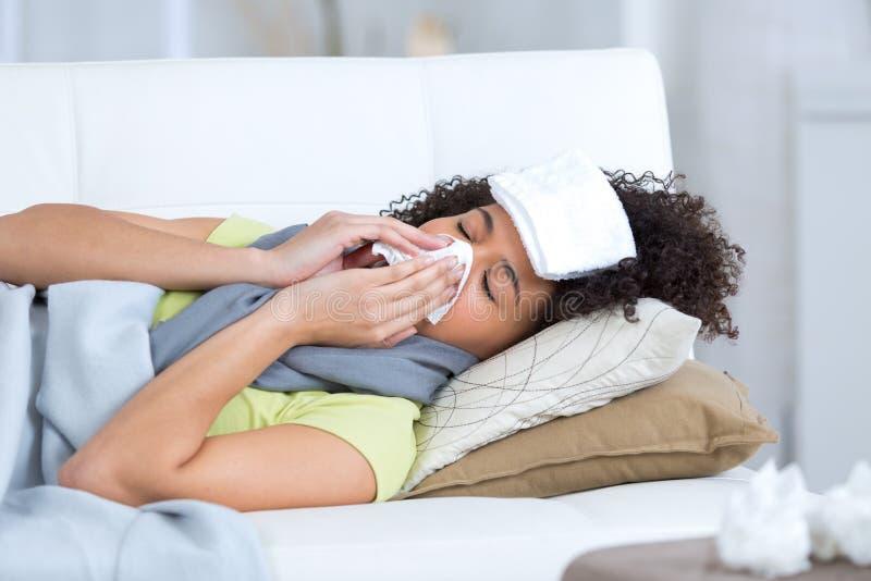 Młodej kobiety choroba na kanapie fotografia royalty free