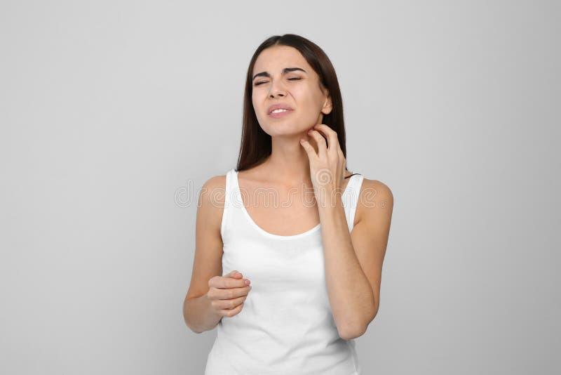 Młodej kobiety chrobotliwa szyja na lekkim tle zdjęcie stock