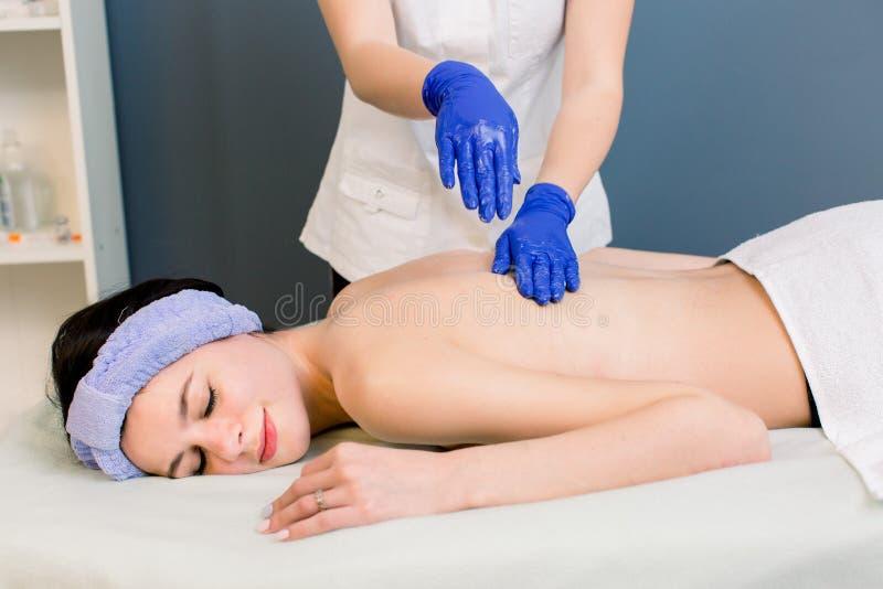 Młodej kobiety cosmetologist robi z powrotem masażowi przy zdroju salonem dla młodej ładnej dziewczyny fotografia stock