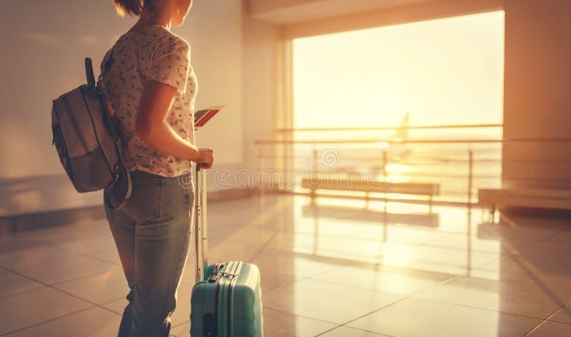 Młodej kobiety czekanie dla latać przy lotniskiem przy okno z suitcas zdjęcia royalty free
