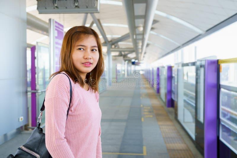 Młodej kobiety czekanie i patrzeć dla niebo pociągu w platformie obrazy royalty free