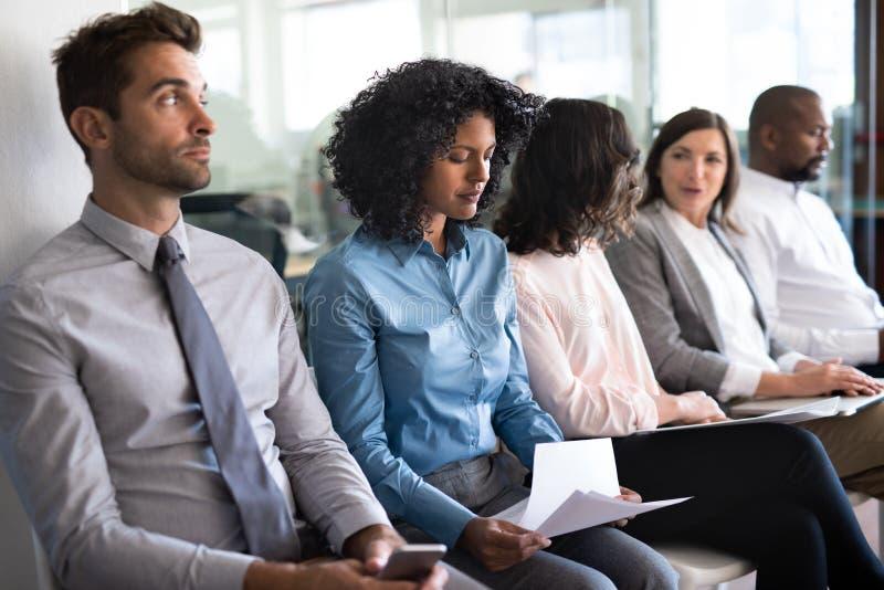 M?odej kobiety czekanie z innymi kandydatami do pracy w biurze zdjęcia stock