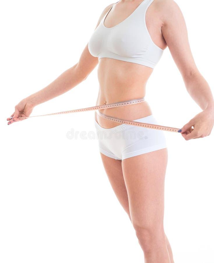 Młodej kobiety czułość dla postaci mierzy jej ciało z taśmą, zdjęcia royalty free