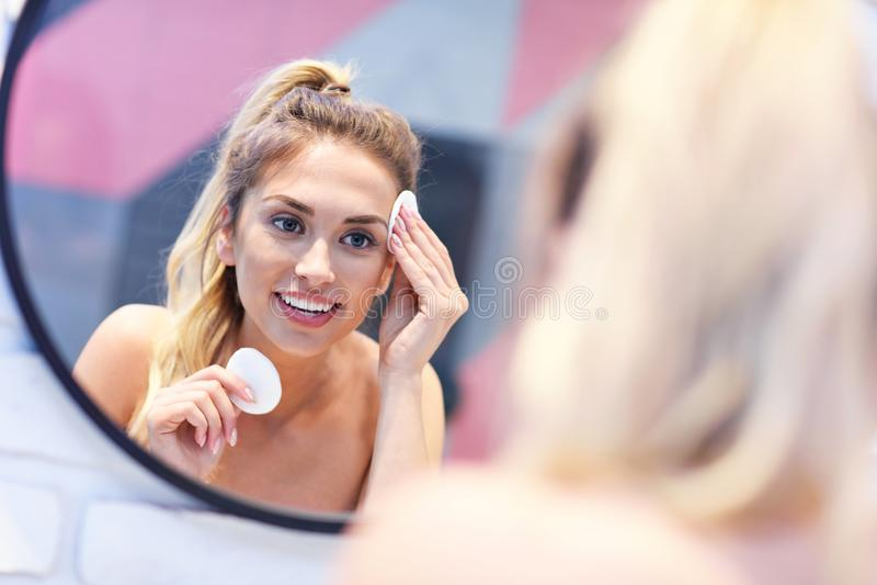 Młodej kobiety czyści twarz w łazienki lustrze fotografia royalty free