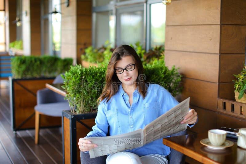 Młodej kobiety czytelnicza gazeta i używać przy restauracją smartphone obraz royalty free