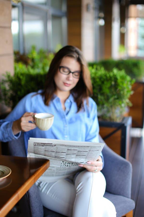 Młodej kobiety czytelnicza gazeta i używać przy restauracją smartphone fotografia royalty free