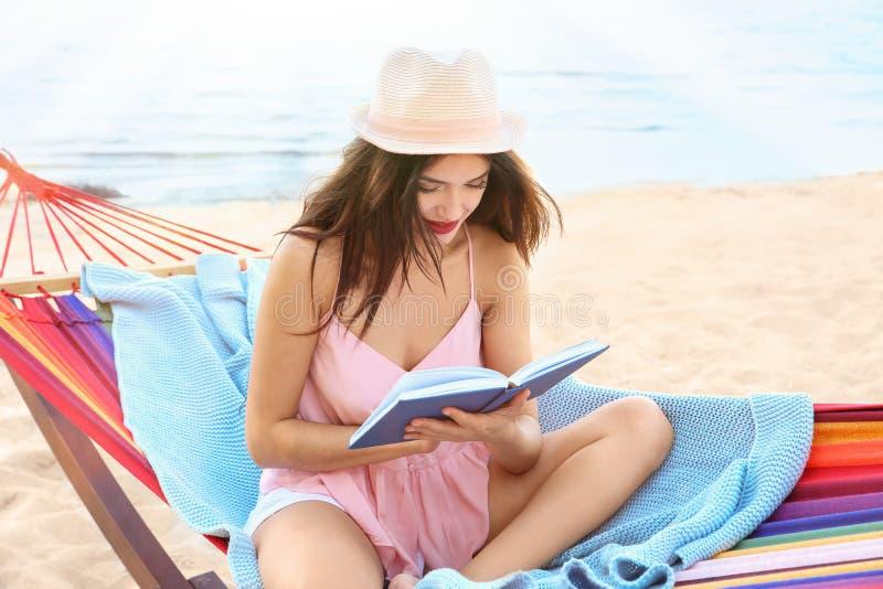 Młodej kobiety czytelnicza książka w hamaku zdjęcia royalty free