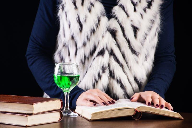 Młodej kobiety czytelnicza książka w zmroku, starej bibliotece i napoju absyncie zdjęcie royalty free