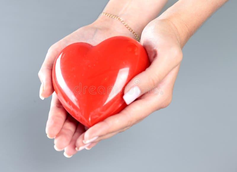 Młodej kobiety doktorski mienie czerwony serce, odizolowywający na bielu zdjęcie royalty free