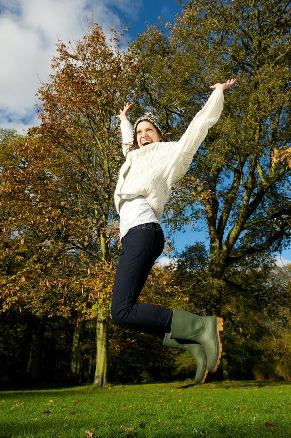 Młodej kobiety doskakiwanie dla radości outdoors na pięknym spadku dniu zdjęcia stock