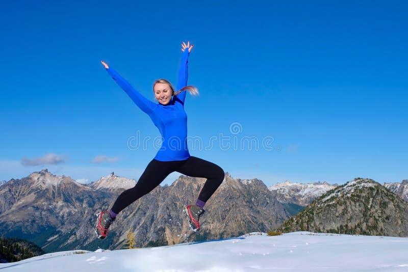 Młodej kobiety doskakiwanie z radością w górach zdjęcie stock