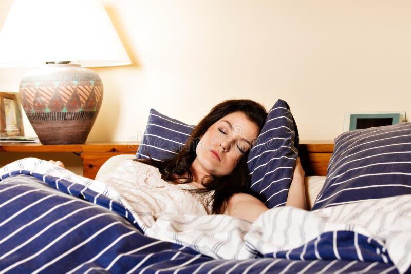 Młodej kobiety dosypianie na białych obleczeniach w łóżku obraz stock
