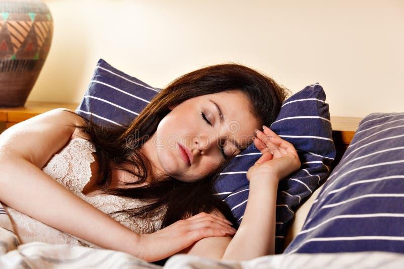 Młodej kobiety dosypianie na białych obleczeniach w łóżku zdjęcia stock