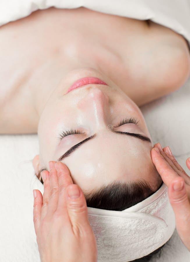 Młodej kobiety głowa i twarz masaż w zdroju salonie obraz stock