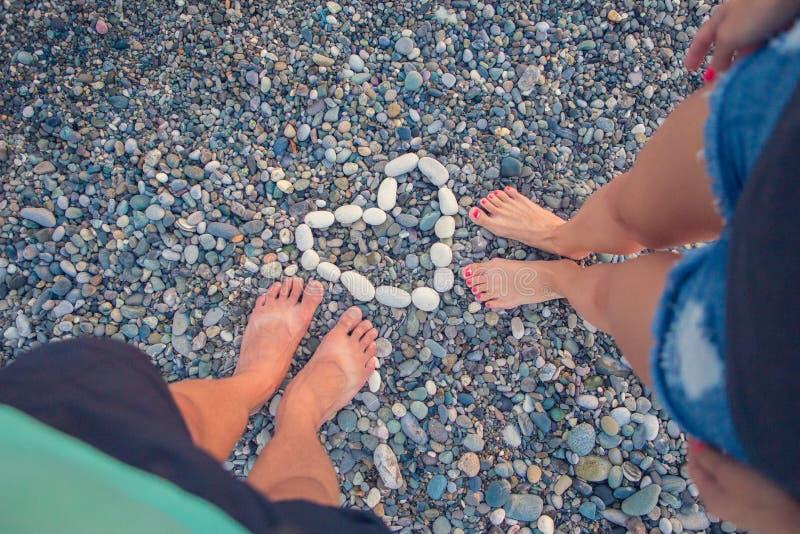 Młodej kobiety i chłopiec pozycja na otoczaka zaokrąglonych kamieniach Dziewczyna i chłopiec cieszy się niezwykłą plażę, otoczaki zdjęcie royalty free