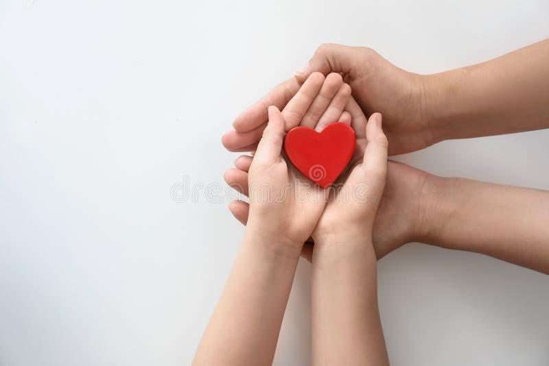 Młodej kobiety i dziecka mienia czerwieni serce zdjęcia stock