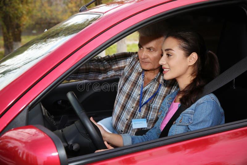 Młodej kobiety i seniora instruktor w samochodzie Przelotny napędowy egzamin zdjęcie stock