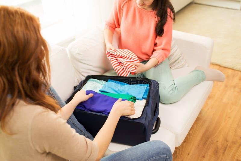 Młodej kobiety kocowanie odziewa w podróży torbę obrazy stock