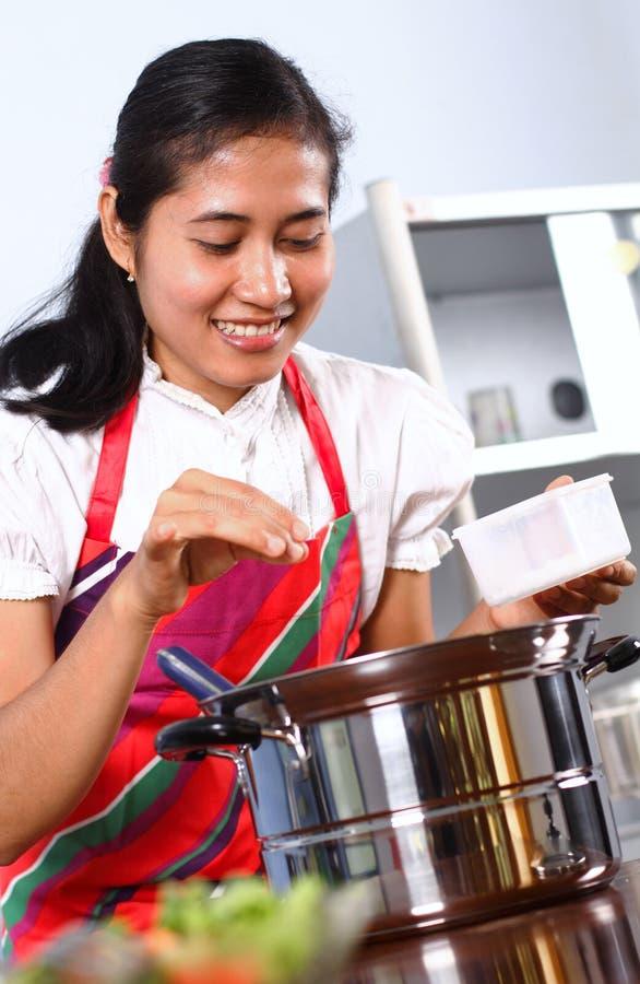 Młodej kobiety kucharstwo w kuchni obrazy royalty free