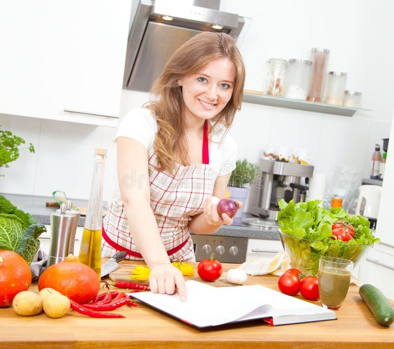 Młodej kobiety kucharstwo w kuchni Zdrowy jedzenie - Jarzynowy Sal zdjęcie stock