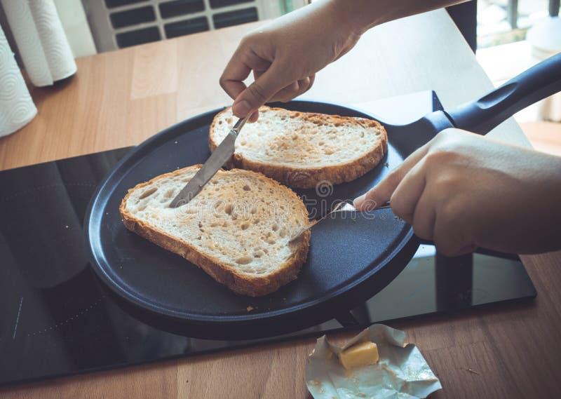 Młodej kobiety kulinarny chlebowy śniadanie na kontuaru baru kuchni obrazy stock