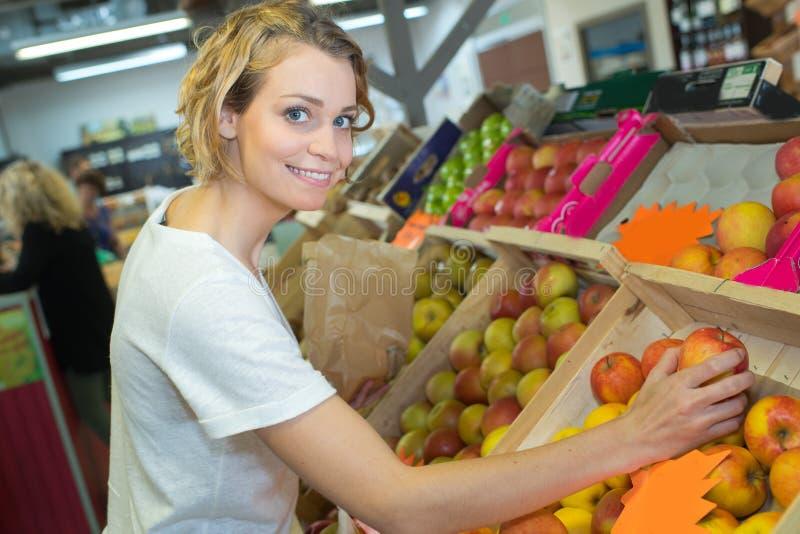 Młodej kobiety kupienia jabłko na rynku fotografia royalty free
