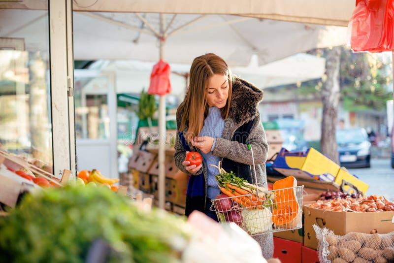 Młodej kobiety kupienia pomidor fotografia royalty free