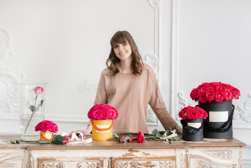 Młodej kobiety kwiaciarni ułożenia rośliny w kwiatu sklepie ludzie, biznes, sprzedaż i floristry pojęcie, Bukiet czerwone róże zdjęcie royalty free