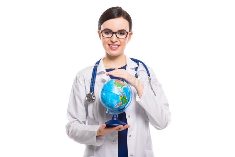 Młodej kobiety lekarka trzyma światową kulę ziemską w jej rękach w bielu mundurze na białym tle z stetoskopem zdjęcie royalty free