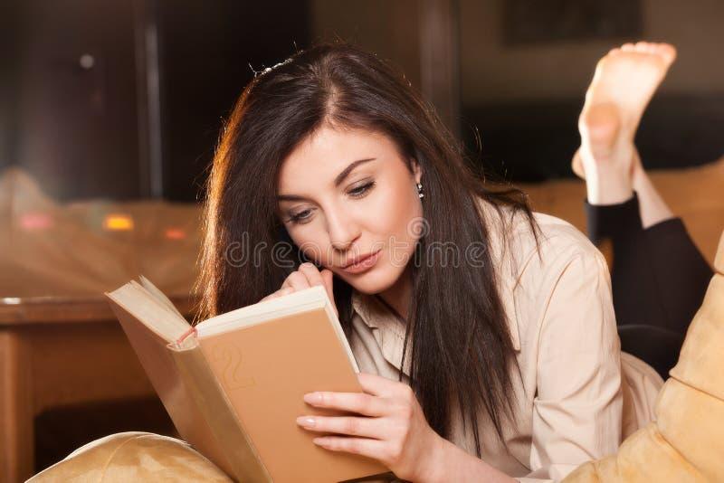 Młodej kobiety lying on the beach na jej leżance czyta książkę w domu obraz stock