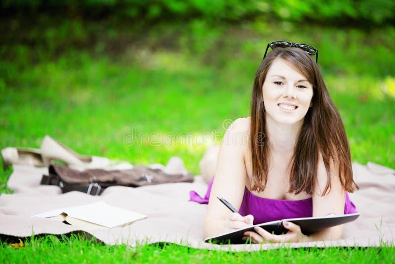 Młodej kobiety lying on the beach na koc w parku i studiowaniu zdjęcie royalty free