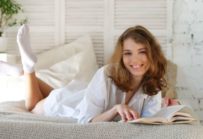 Młodej Kobiety lying on the beach w łóżku podczas gdy czytający książkę zdjęcie stock