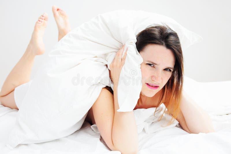 Młodej kobiety lying on the beach w łóżku z migreną zdjęcia stock