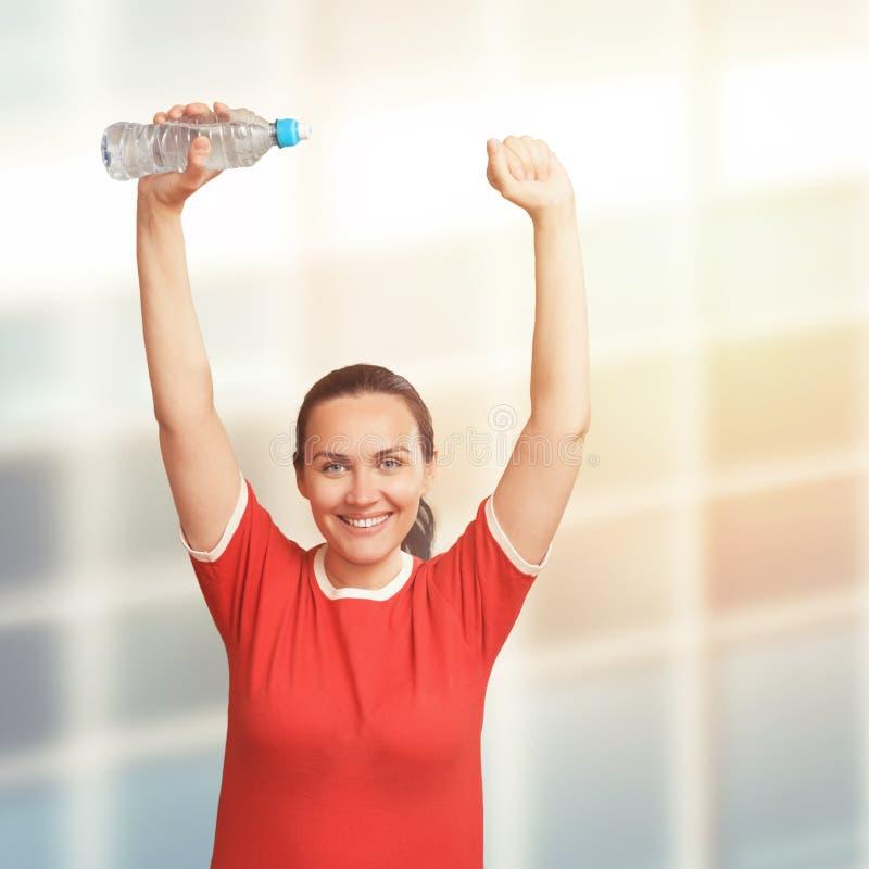 Młodej kobiety mienia butelka wewnątrz oddawał jej głowę ręce do góry zdjęcie royalty free
