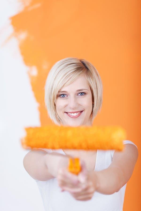 Młodej Kobiety mienia farby rolownik Przeciw połówka Malującej ścianie obrazy royalty free