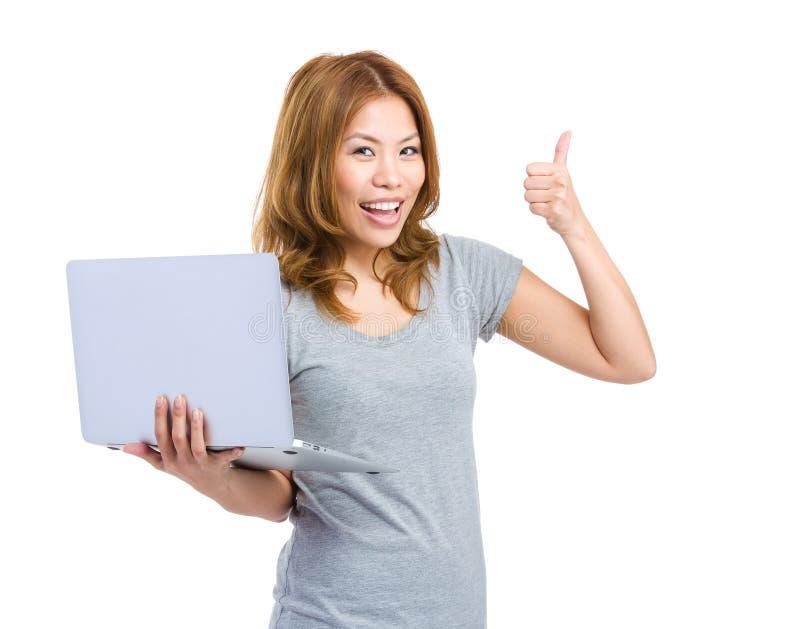 Młodej kobiety mienia laptop robi kciukowi up zdjęcia royalty free