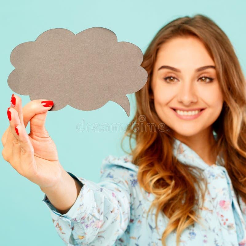 Młodej kobiety mienia myśli pusty bąbel nad błękitnym tłem zdjęcie royalty free