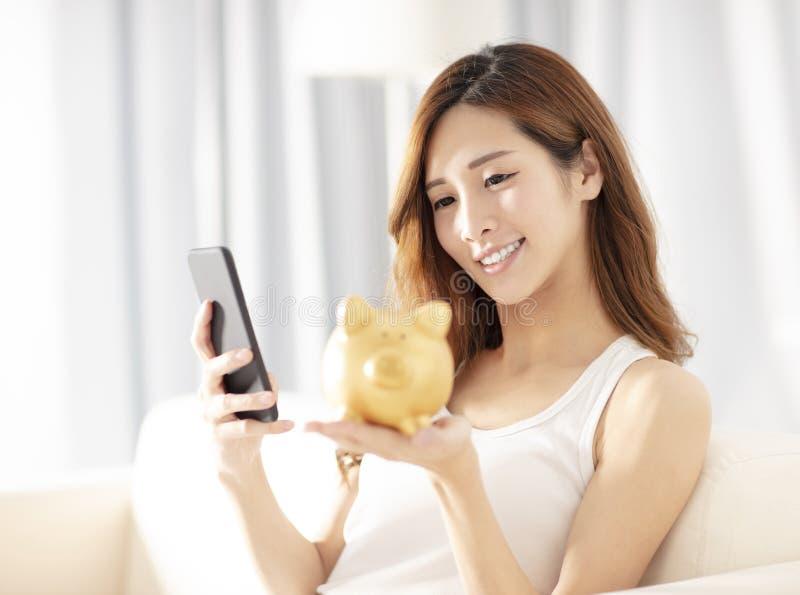 młodej kobiety mienia prosiątka bank patrzeje mądrze telefon zdjęcia stock