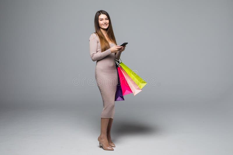 Młodej kobiety mienia torba na zakupy i use telefon komórkowy odizolowywający na popielatym tle obraz stock