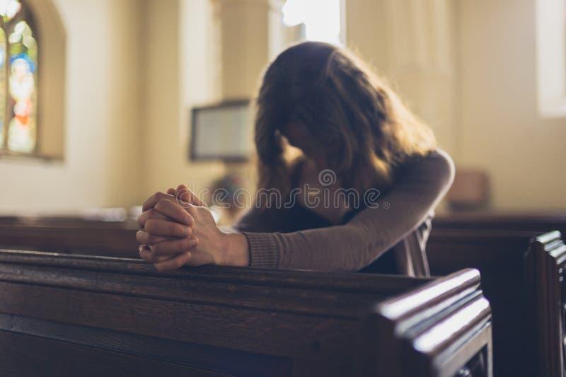 Młodej kobiety modlenie w kościół zdjęcie stock