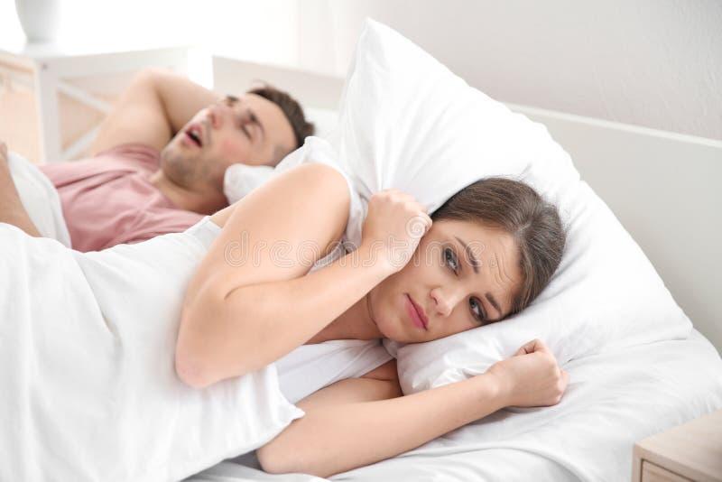 Młodej kobiety nakrycia głowa z poduszką przez jej męża chrapania obrazy stock