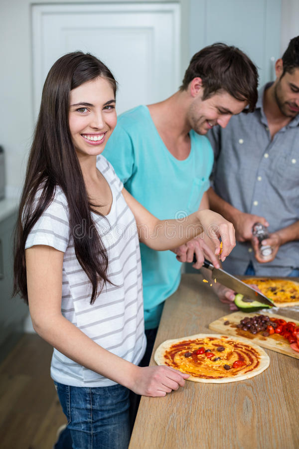 Młodej kobiety narządzania pizza podczas gdy przyjaciele w tle zdjęcie royalty free