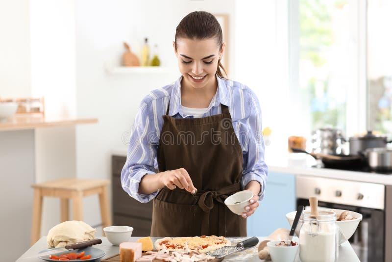 Młodej kobiety narządzania pizza w kuchni fotografia stock