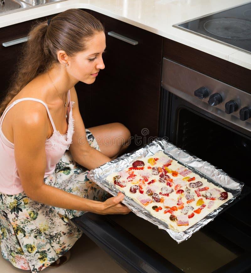 Młodej kobiety narządzania pizza z salami fotografia stock