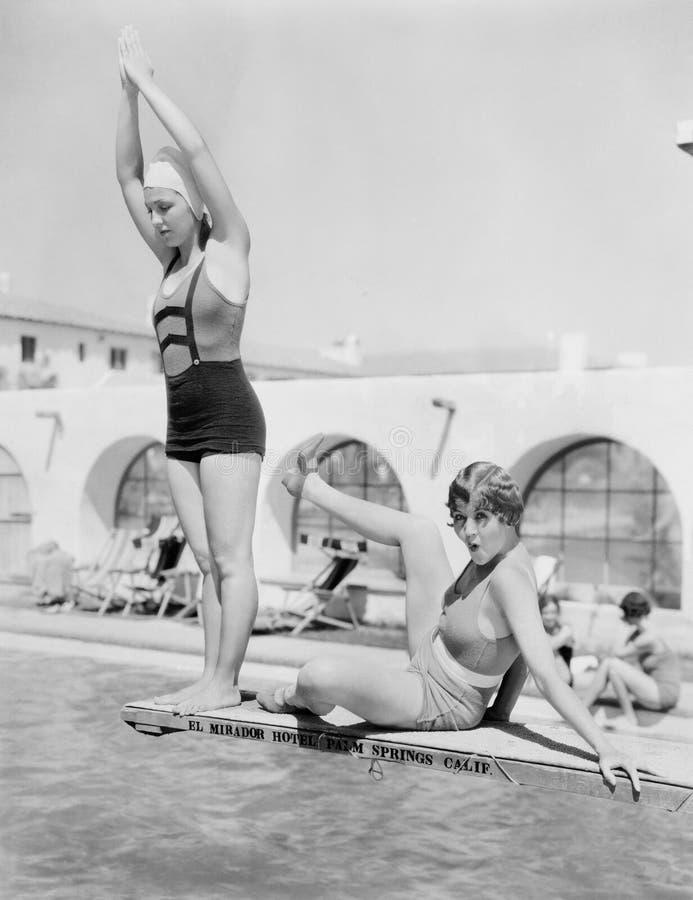 Młodej kobiety narządzanie nurkować od nurkowej platformy z innym kobiety obsiadaniem obok ona (Wszystkie persons przedstawiający obraz royalty free
