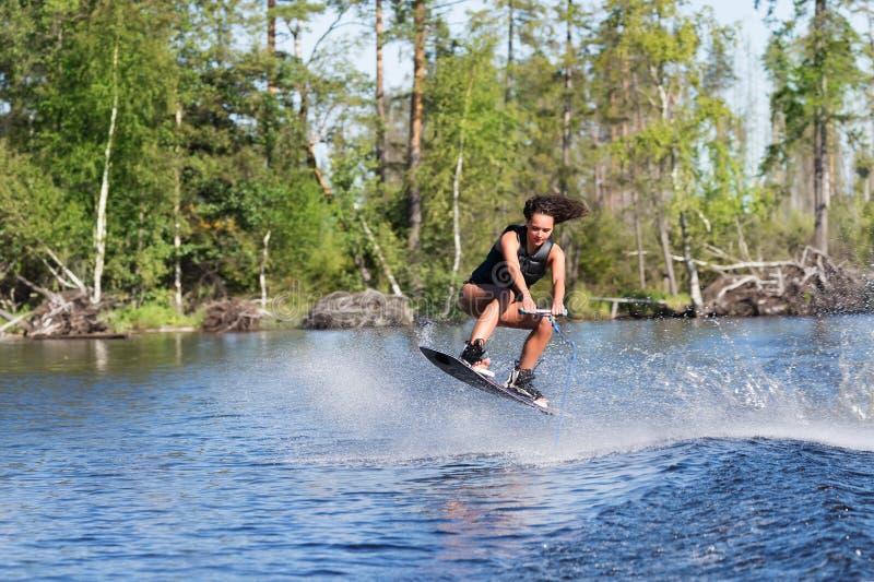 Młodej kobiety nauki jazda wakeboarding na jeziorze zdjęcia stock