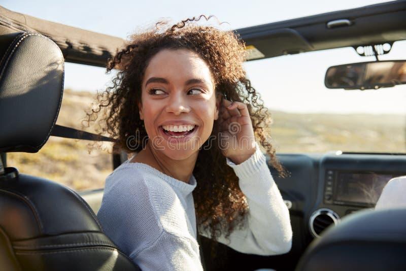 Młodej kobiety obracać round w frontowym miejscu pasażera samochód fotografia royalty free