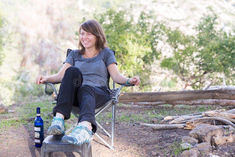 Młodej kobiety obsiadania krzesło w lesie fotografia royalty free