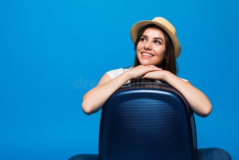 Młodej Kobiety obsiadanie blisko walizka bagażu na błękitnym tle zdjęcie royalty free