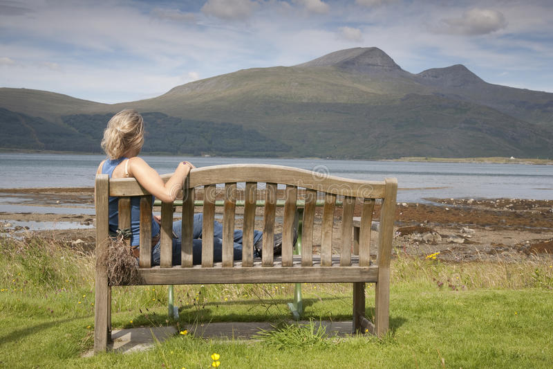 Młodej Kobiety obsiadanie na ławce zdjęcia stock